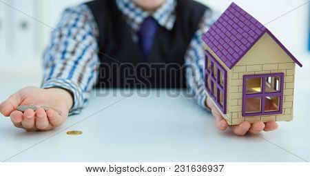 Plastic House Toy And Money In Little Boy's Hands. Invest In Real Estate.