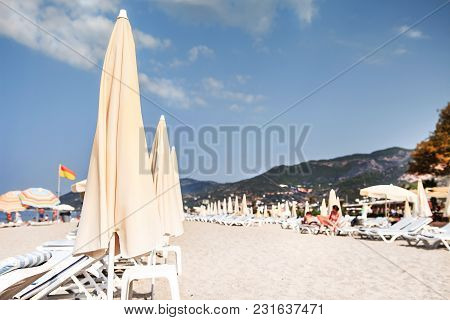 Tropical Resort Sandy Beach Soft Selective Focus. Beach With Sun Umbrellas And Deck Chair Or Sunbeds