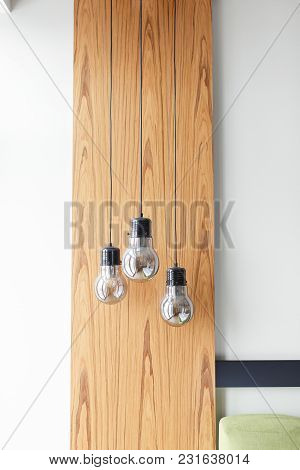 Light Bulbs On Wooden Panel Background Isolated On White Wall. Modern Style Bedroom Interior Decor.