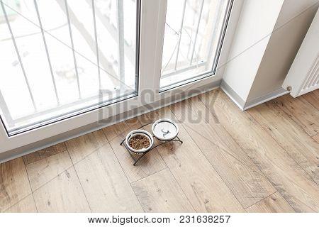Dog Food In Bowl On Wooden Floor Near Window.