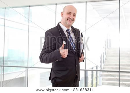 happy male doctor going thumb up, at the hospital