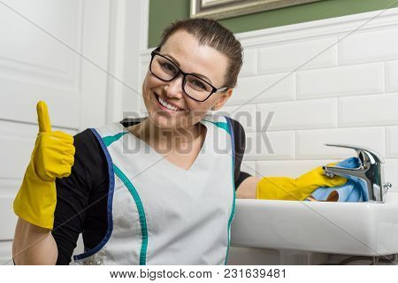 Woman In Cleaning Clothes Giving Thumbs Up. Background Bathroom.
