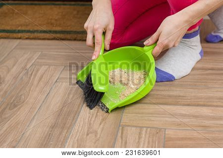 Close-up Of Woman Cleaning Floor With Broom And Dust Pan.