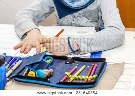 Left Handed Young Boy Working On His Homework.
