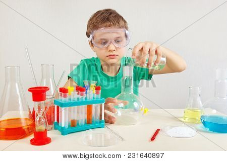 Little Chemist In Safety Goggles Doing Chemical Experiments In The Laboratory