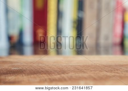 Wooden Table And Blur Bookshelf In Background