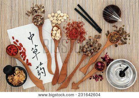 Chinese acupuncture needles and moxa sticks used in moxibustion therapy with herbs and calligraphy script on rice paper. Translation reads as chinese herbs. Top view on bamboo.