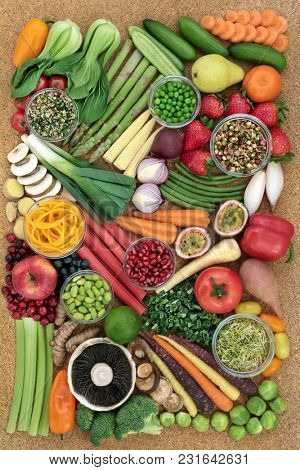 Super food for a healthy life with fresh fruit and vegetables high in antioxidants, anthocyanins, dietary fibre, protein, vitamins and minerals. On cork background, top view.