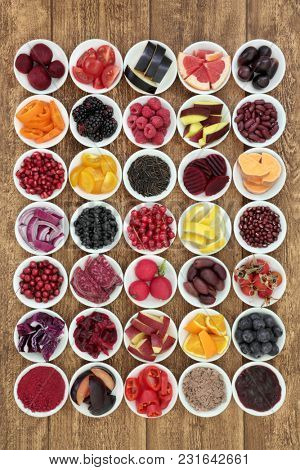 Large healthy food collection with super health promoting properties with foods very high in anthocyanins, antioxidants, protein, minerals and vitamins, on rustic background top view.