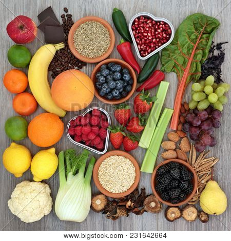 Diet health food concept with fresh fruit, vegetables, coffee, grains, nuts, chocolate, ginseng and tribulus terrestris herbal medicine used as an appetite suppressant and aphrodisiac. Top view.