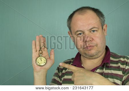 A Man Is Pointing At A Mechanical Pocket Watch In His Hand On A Light Green Background
