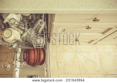 Dishwasher Full With Clean Dishes In Kitchen Background, Copy Space