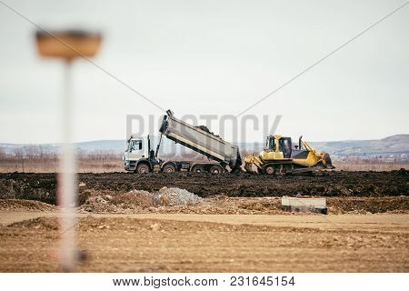 Highway Construction Site Development With Dumper Truck Dumping Earth And Bulldozer Leveling And Pus