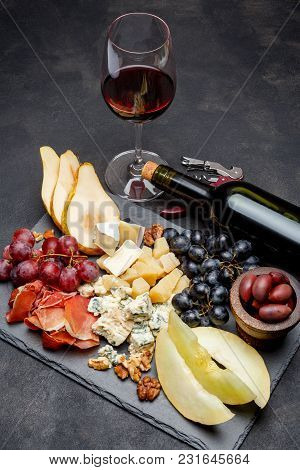 Meat Plate Antipasti Snack With Prosciutto Ham, Blue Cheese, Melon, Grapes, Olives On Stone Serving