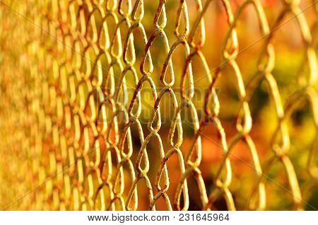 Old Rusty Chain-link Fence At Orange Sunset