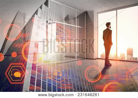 Businessman Looking Out Of Window In Interior With Abstract Business Interface And City View. Financ