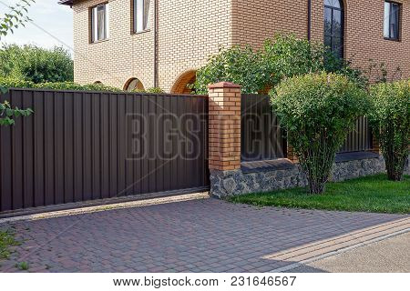 Iron Closed Gates On A Brick And Fence In Grass And Green Vegetation