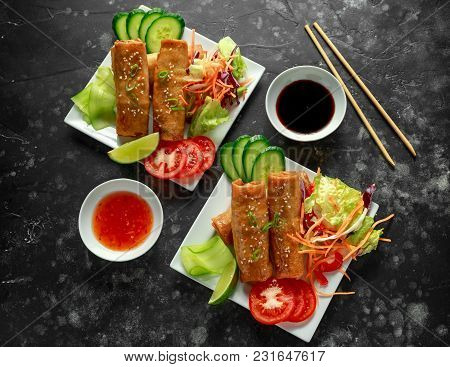 Chinese Vegetable Spring Rolls Garnished With Fresh Salad, Lime Wedges, Sweet Chilli Sauce And Soy S