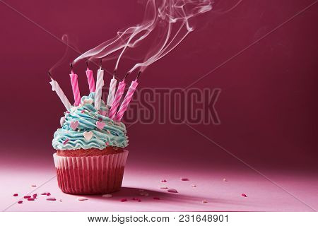 Muffin With Cream And Extinguished Candle. The Concept Of The End Of The Celebration.