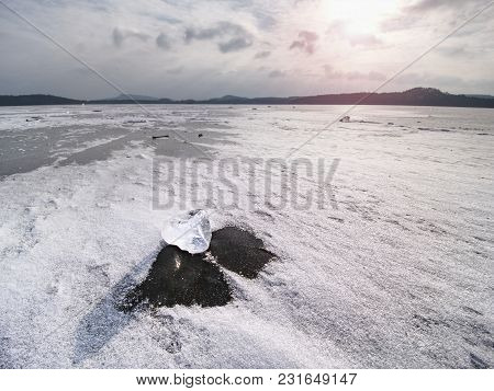 Drifting Piece Of Iceberg And Sun Glaring On Thick Ice Cover.  Drifting Ice Floes On  River.