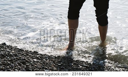 Man In Pants Walks Into The Sea To Soak His Feet And Goes To The Land
