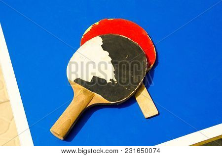 A Two Old Tennis Rackets On The Table