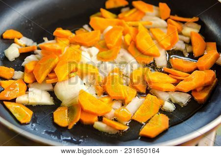 A Carrot And Onion Frying In Pan