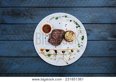 Steak Pepper From Veal With Grilled Vegetables, Served In A Ceramic White Plate With Wooden Backgrou