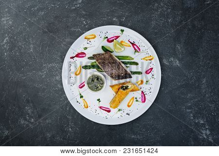 Fillet Of Black Cod With Asparagus And Cheese With Honey-ginger Sauce, Served In A Ceramic White Pla