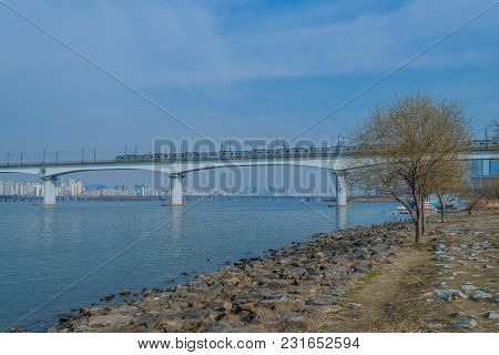 River Landscape With Subway Train Crossing Bridge Over River In The Background Under Clear Blue Skie