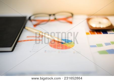 Business Concept Of Office Working And Analysis Graphics And Clock On Table