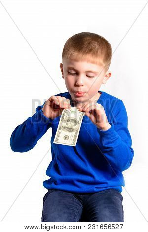 A Little Boy In A Blue Jacket Holds A Hundred Dollars, Isolated On A White Background