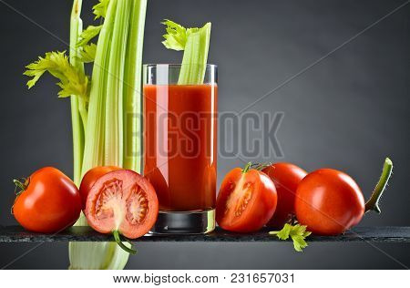 Tomato Juice Or Cocktail Bloody Mary With Tomatoes And Celery Sticks On A Dark Background. Copy Spac