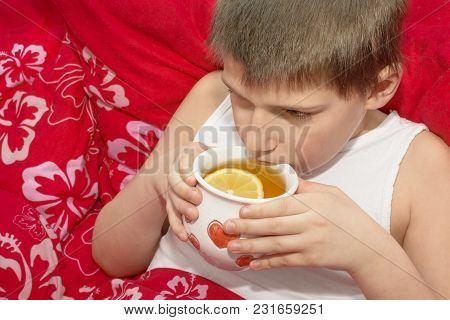 A Sick Boy Holding A Cup With A Hot Lemon Tea