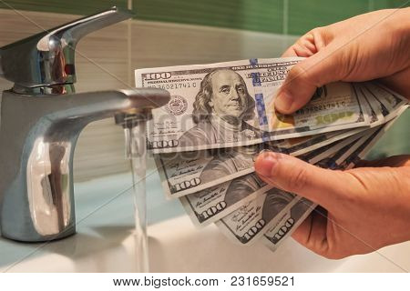 Money Launder. Us Dollars Hung Under Running Tap Water As A Metaphor For Money Laundering. Black, Ma