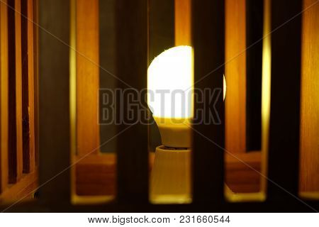 Closeup Of Fluorescent Sphere Lamp Turning On In The Wooden Cage, Concept Of Blocking  Idea