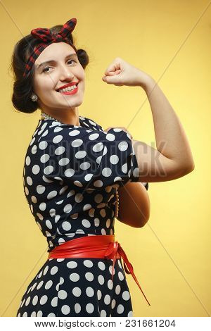 Strong Woman Show Her Biceps On Yellow Background Looking At Camera