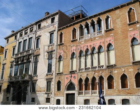 Venice. Italy. Beautiful Old Buildings With Balconies, Columns, Stylish Windows. The Sun Illuminates