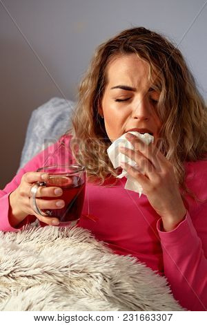 Young Woman Sick In Bed With Temperature Drinks Hot Tea At Home