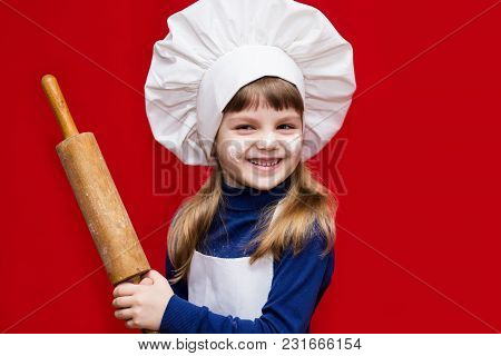 Happy Little Girl In Chef Uniform Holds Rolling Pin Isolated On Red. Kid Chef. Cooking Process Conce