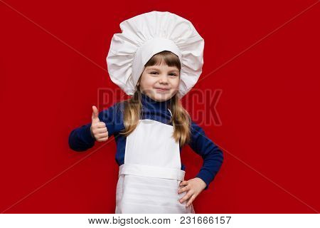 Happy Little Girl In Chef Uniform With Thumb Up Isolated On Red. Kid Chef. Cooking Process Concept