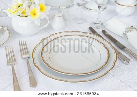 Classic Serving For A Gala Dinner With Luxurious Porcelain, Silverware And Spring Flowers On A White