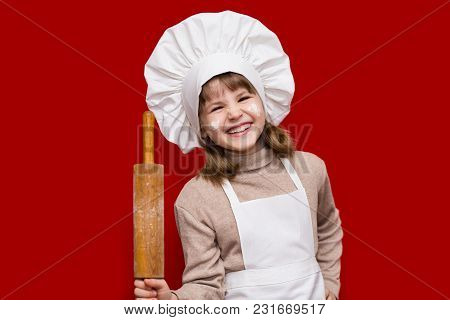 Portrait Of Happy Little Girl In Chef Uniform Holds A Rolling Pin Isolated On Red. Kid Chef. Cooking