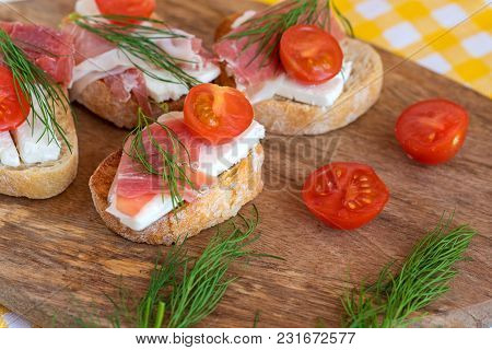 Italian Prosciutto And Feta Cheese Bruschetta Decorated By Tomato And Dill. Antipasti On Grilled Bag