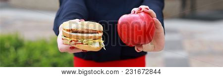 What To Choose. Healthy And Unhealthy Food, Female Hands Holding A Hamburger And An Apple, Standing