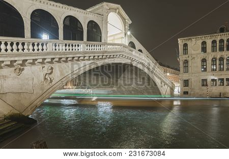 Famous Rialto Bridge By Night With Ship Light Traces Above Waters Of Grand Canal