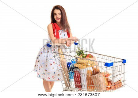 A Young Female Pushing A Shopping Cart Full With Groceries Isolated On White Background. Brunette In