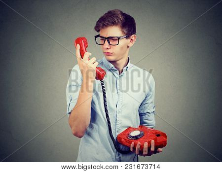 Confused Worried Teenager Man Looking At Old Fashioned Telephone
