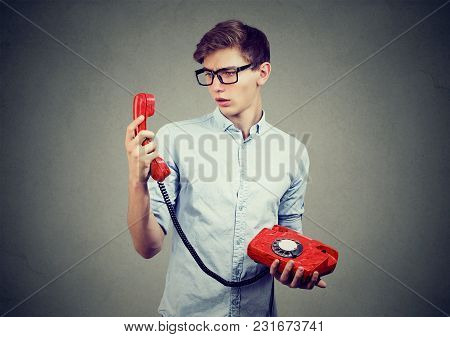 Confused Teenager Man Looking At Old Fashioned Telephone