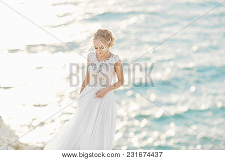 Beautiful Young Blonde Model Girl, In White Lace Dress, Stands At The Sea Coast.